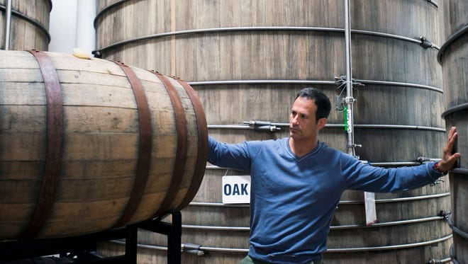 Dogfish Head founder Sam Calagione checks on barrels of aging beer at the Milton brewery.