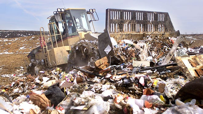 A compactor runs over a pile of garbage at the Iowa City landfill.