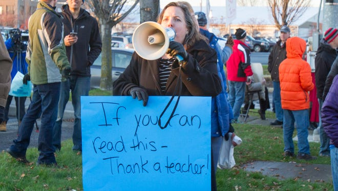A teacher calls out instructions to the more than 400 teachers assembled for higher pay on Monday afternoon.