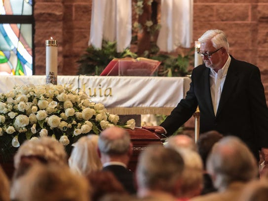 Peter Armstrong puts a hand on the casket as he returns