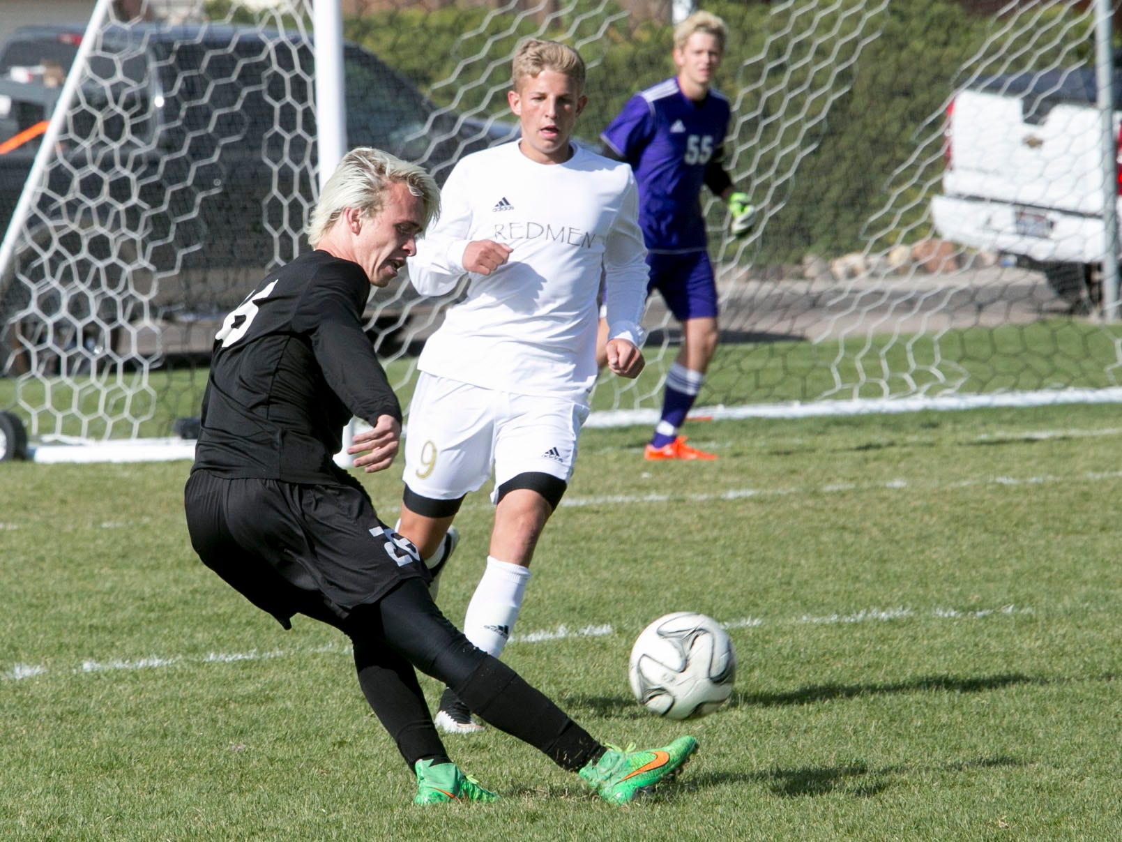 Desert Hills' Kanon Heaton scores against Cedar's Andrew Boyer on Friday at Cedar High School.