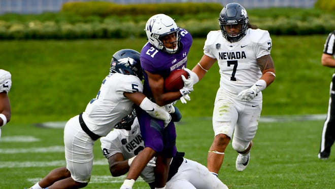 Dameon Baber (5), defensive end Malik Reed (90) and Gabe Sewell (7) try to take down Northwestern running back Justin Jackson last season.