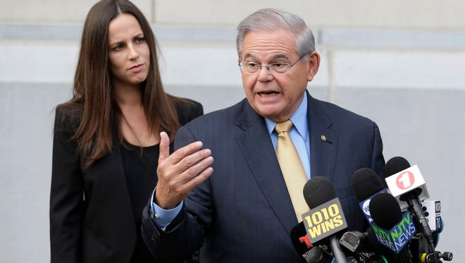 Sen. Bob Menendez talks to reporters as he arrives to court for his federal corruption trial in Newark, N.J., as his daughter Alicia Menendez looks on.