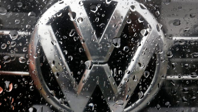 The Volkswagen logo is photographed through rain drops on a window in Frankfurt, Germany, Friday, Nov. 18, 2016. Automaker Volkswagen said Friday it will shed 30,000 jobs to cut costs as it tries to recover from its diesel emissions scandal and invests more in electric-powered vehicles and digital services. Company officials said at a news conference at headquarters in Wolfsburg, Germany, that 23,000 of the job cuts will come in Germany. It said the measures will save some 3.7 billion euros (US $4 billion) a year from 2020.  (AP Photo/Michael Probst)