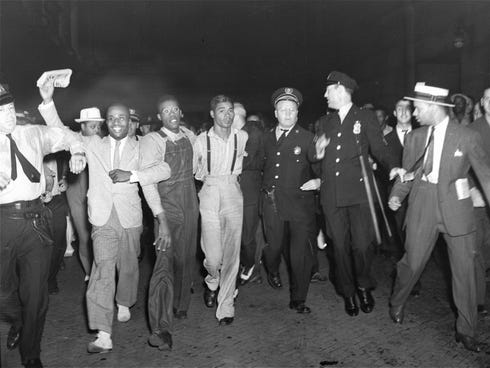 In this July 26, 1937 file photo, police escort two of the five recently freed