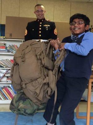 Rishi Lakkakula grins as he struggles to lift Mowen's 70-pound backpack.