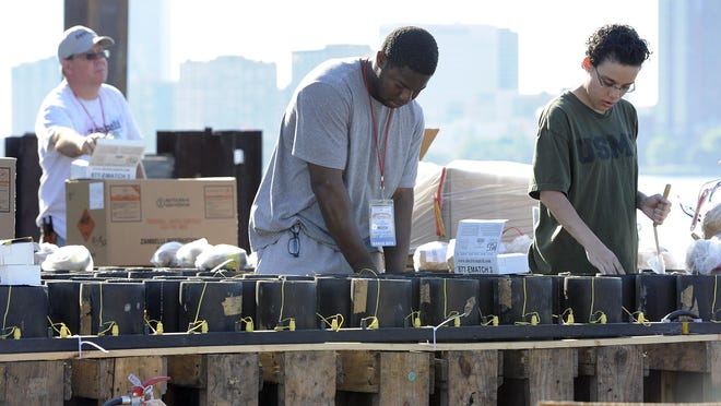 Zambelli pyrotechnicians work Saturday on 11,000 mortars that will be set off during The Ford Fireworks on Monday. The mortars are divided up over three barges.