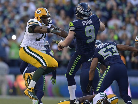 Green Bay Packers defensive tackle Mike Daniels (76) runs into Seattle Seahawks punter Jon Ryan (9) in the first quarter during their Week 1 game at CenturyLink Field in Seattle. Daniels was called for a penalty on the play.