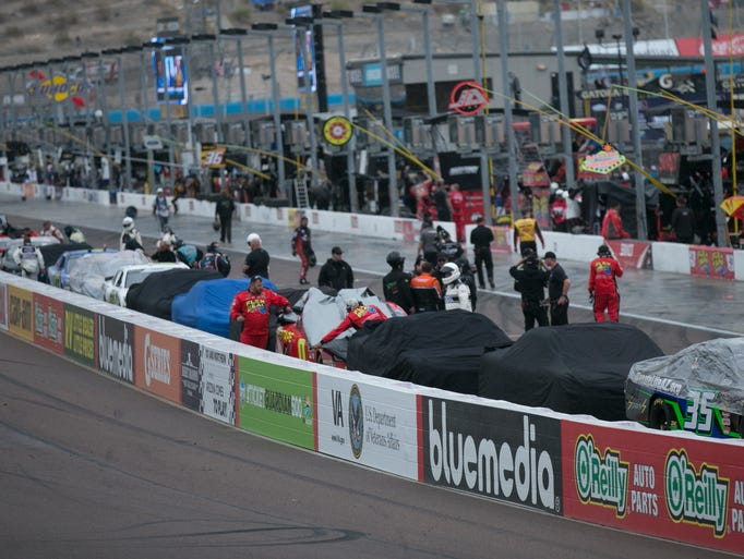 Cars are stopped for a red flag as it begins to rain