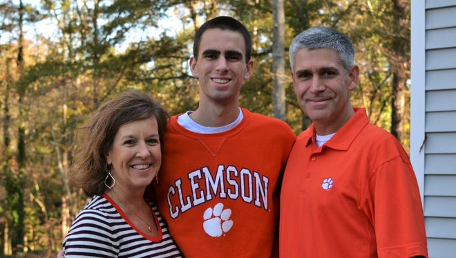 Clary Miles, center, stands with his parents Paula and Kevin outside of their home in Clemson on Friday, November 17, 2017. Clary Miles, 19, survived a car accident on Oct. 3 and was rescued from his vehicle by members of the Clemson University Football team.