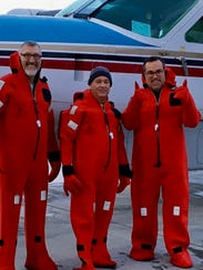 Mick Beale, middle, and his son, right, recently flew more than 10,000 miles around the world. They had to wear those strange looking suits because of how cold it was outside.