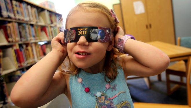 Emmalyn Johnson, 3, tries on her free pair of eclipse glasses at Mauney Memorial Library in Kings Mountain, N.C. on August 2, 2017.