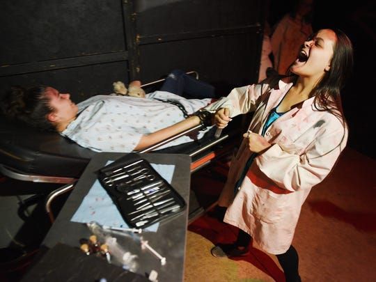 Jaden Wieser, right, prepares to put a syringe into Elizabeth Searles, left, during Jaycees Haunted House in 2017.