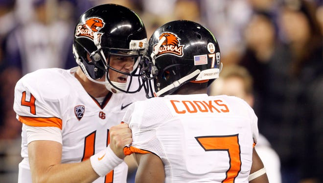Oregon State Beavers wide receiver Brandin Cooks (7) and quarterback Sean Mannion (4) celebrate a 54-yard touchdown pass and reception, respectively, against the Washington Huskies during the third quarter at CenturyLink Field.