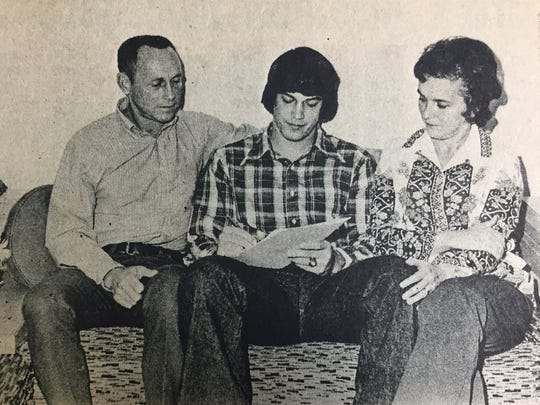 Jim Joiner, halfback for the Union County Braves, with his parents, Mr. and Mrs. James Joiner, look over the contract he signed with Murray State University in December 1973.