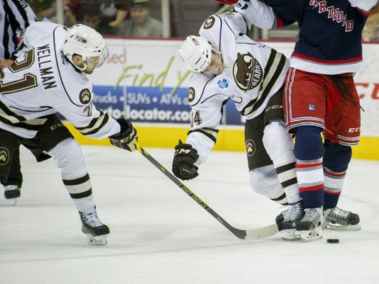Hershey's Casey Wellman (21) and Jim O'Brien (14) tie up Hartford defenseman Michael Kostka in the first period of Game 2 of their Eastern Conference semifinal series on Friday at Giant Center. The Bears went on to win, 6-4.