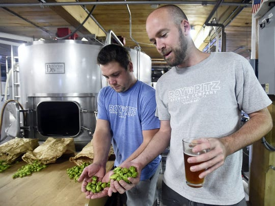 A file photo of Ryan Richards (left), co-founder of Roy-Pitz Brewing Company, and Chris Collier (right), head brewer, showing some local hops they used to create a lager at the brewery in Chambersburg.