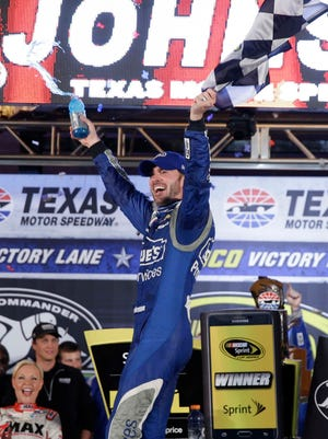 Jimmie Johnson celebrates winning the NASCAR Sprint Cup auto race at Texas Motor Speedway in Fort Worth, Texas, Saturday, April 11, 2015. (AP Photo/Tim Sharp)