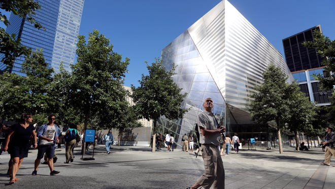 In this Sept. 6, 2013, file photo, a visitor to the National September 11 Memorial and Museum walks past the museum in New York. The long-awaited museum dedicated to the victims of the Sept. 11 terror attacks will open to the public at the World Trade Center site on May 21, officials announced Monday, March 24, 2014.)