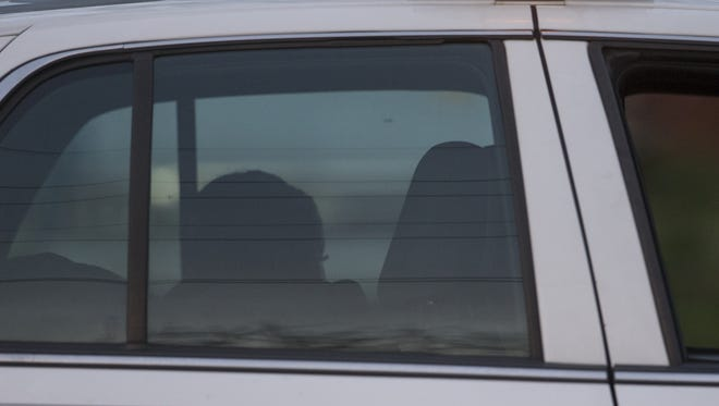 A young woman sits in a cop car at the scene of a death on the 2300 block of North Raceway Road, Indianapolis, Sunday, April 9, 2017.