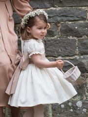 Princess Charlotte wore flowers in her hair and an ivory silk dress with a frilly collar and a huge pink-nude bow in the back for her aunt Pippa Middleton's wedding. She carried a basket as she stopped with her mother in front of St Mark's Church in Englefield, England.