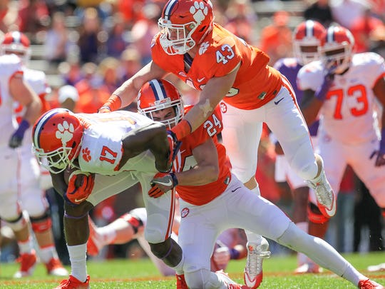 Clemson linebacker Chad Smith (43), right, and Clemson defensive back Nolan Turner(24) tackle Clemson wide receiver Cornell Powell (17) during Clemson's NCAA college football spring game at Memorial Stadium in Clemson, S.C. on Saturday, April 8, 2017.