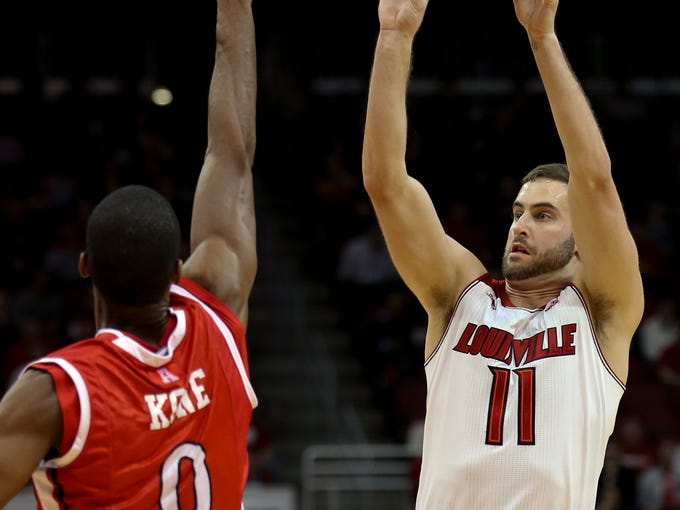 Louisville's Luke Hancock knocks down one of his six three pointers over top of Rutgers' Malick Kone.  Feb. 16, 2014