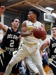 In this file photo taken earlier this season, York Catholic senior D'Andre Davis shoots drives against Delone Catholic. Davis is one of 19 senior boys' basketball players from the region committed to playing in the charitable 'More Than a Game' all-star contest scheduled for May.