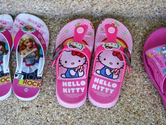 'Hello Kitty' and Barbie flip-flops sit outside a home