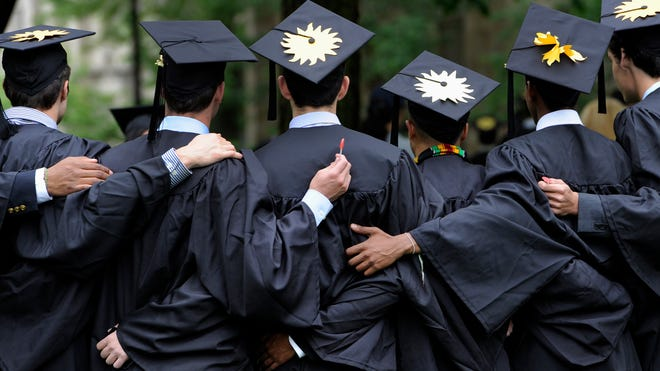 Graduates celebrate during commencement on May 20, 2013,  at Yale University in New Haven, Conn. A new report from Sallie Mae says families are borrowing less to pay for college.