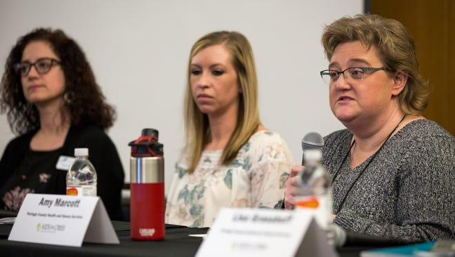 Panelist Amy Marcott, right, division manager of Community Programs for Portage County Health and Human Services, answers questions during the Kids in Crisis town hall in Stevens Point, Wis., Thursday, March 22, 2018.