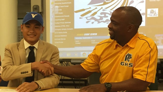 In this Aug. 5 file photo, Jujuan King shakes hands with Guam High football coach Jacob Dowdell after the teen signed a letter of intent to play at North Park University. Dowdell is hoping to get more Guam athletes opportunities to play at the collegiate level