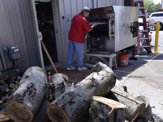 Stacks of fruitwood in the foreground as co-owner Regan Louchart tends the smoker at the newly opened Capital City BBQ on West Saginaw and MLK Blvd., in Lansing.