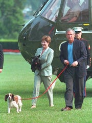 President George W. Bush and first lady Laura Bush exiting Marine One. Mrs. Bush is carrying Barney while President Bush walks Spot.
