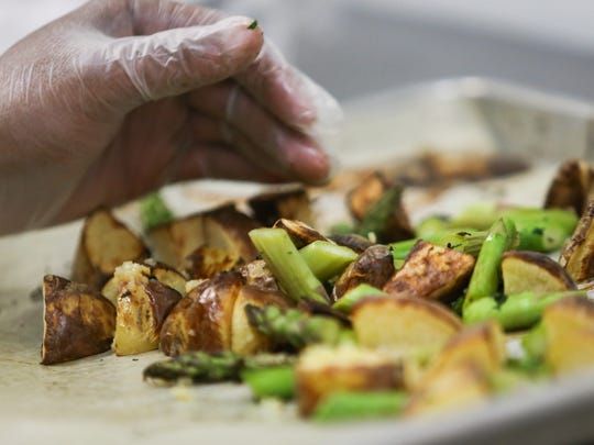 A side dish of roasted potatoes and asparagus is prepared.