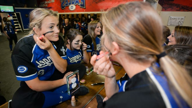 Blakley Cangemi applies her eye black stick as she and her teammates get ready for their game against Haughton.