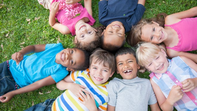 A multi-ethnic group of elementary age children are lying in the grass at the park. They have their heads together in the middle of a circle and are smiling and looking up at the camera.