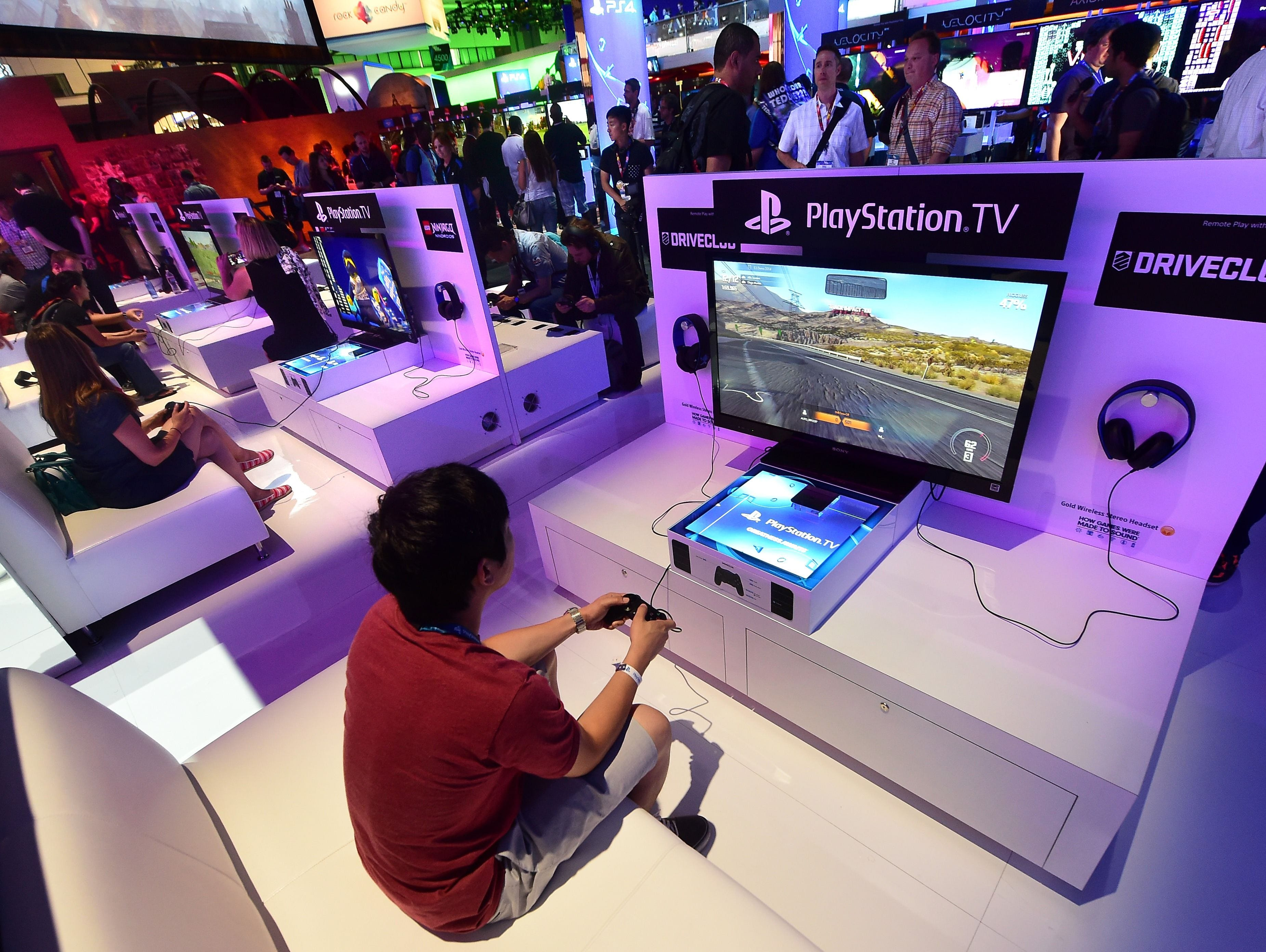 A file photo taken on June 10, 2014 shows people testing the new Playstation TV consoles at the annual E3 video game extravaganza in Los Angeles, Calif.