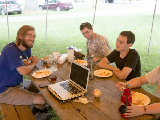 A group of GrassRoots festival volunteers relax over lunch at the Trumansburg Fairgrounds.