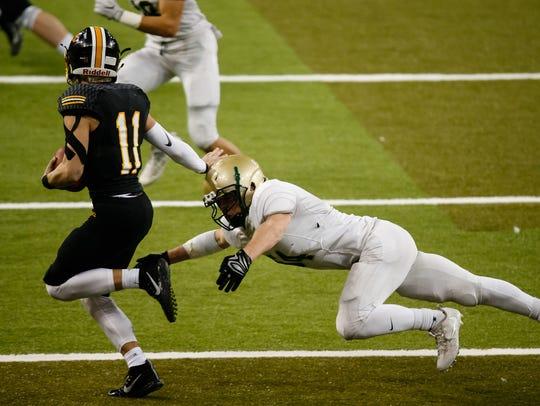 Bettendorf's Carter Bell (11) runs around the tackle