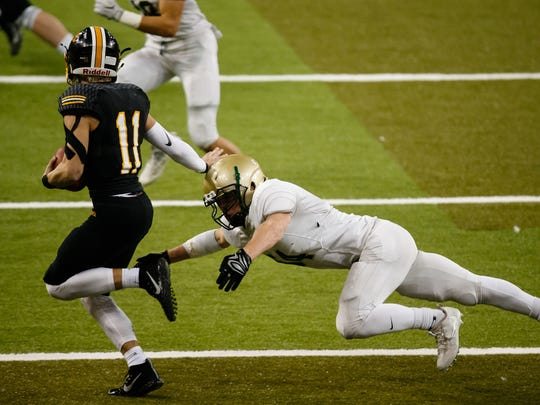 Bettendorf's Carter Bell (11) runs around the tackle of Iowa City, West's Caden Fedeler (54) during their 4A state semi-final football game at the UNI Dome on Friday, Nov. 10, 2017, in Cedar Falls. Iowa City, West would go on to win 23-0 to advance to the state finals.