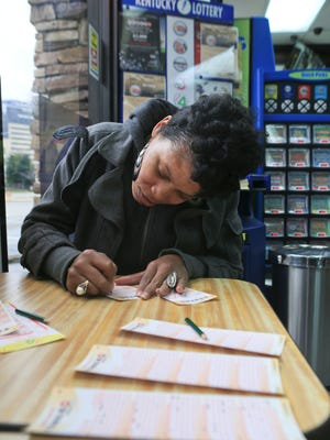 Nicole Williams scratches in her numbers for Powerball tickets at Bader's Food Mart in downtown Louisville before Saturday's Powerball drawing. She said if she won she'd like to travel with her children, open up a boutique and give back.