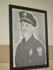 Bishop Flaget student Brandon Smith sketched this drawing of Chillicothe police officer Larry Cox that hangs in the lobby of the Parsons Avenue school. Cox was killed while chasing a suspect in April 2005.