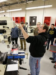 Lead teacher Paul Lindberg demonstrates a mill to students
