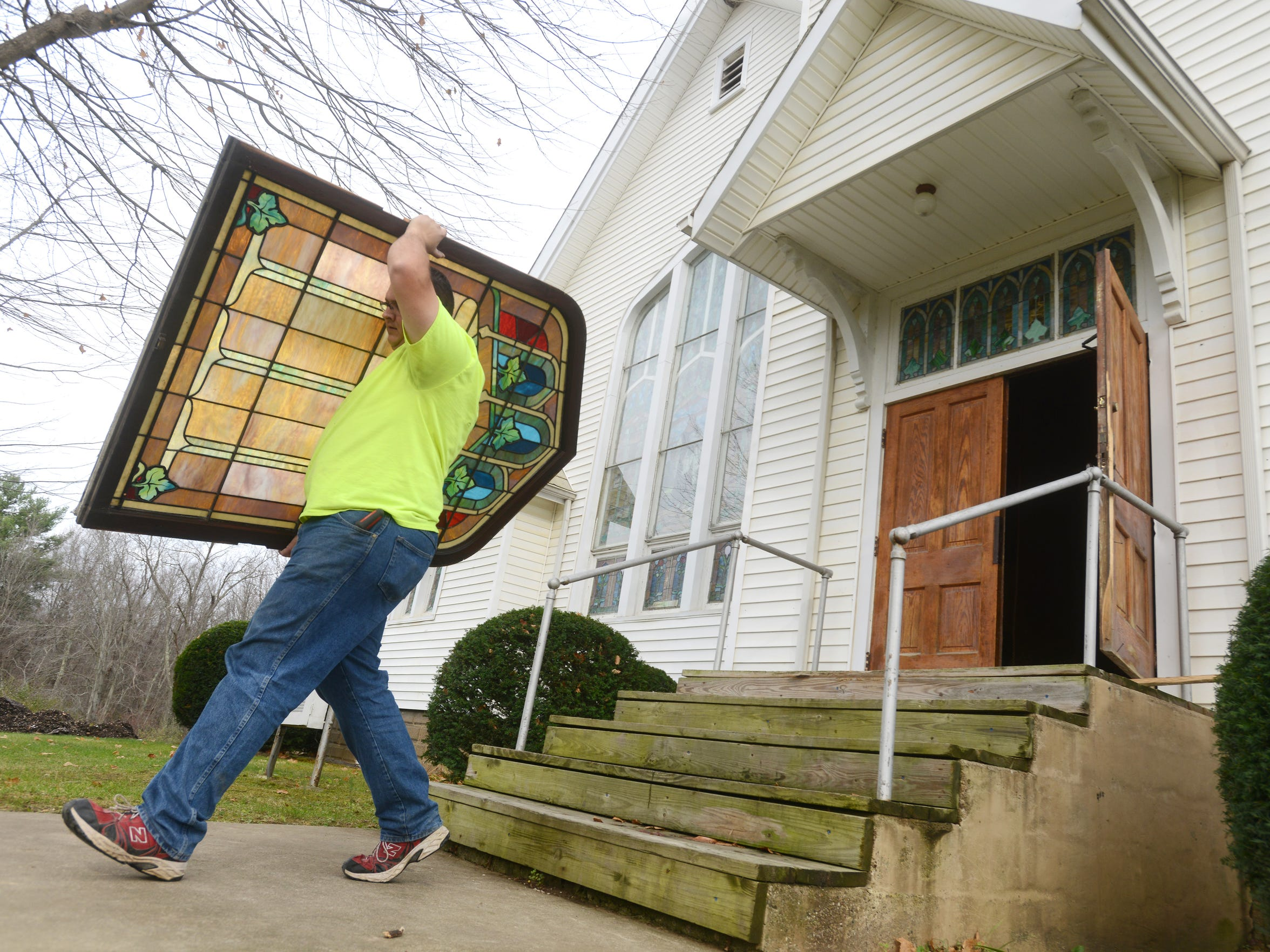 Bryan Hamilton carries a stained glass window from Zion Lutheran Church. The stained glass, organ, pews and other items were removed from the church prior to demolition, and most have found new homes.