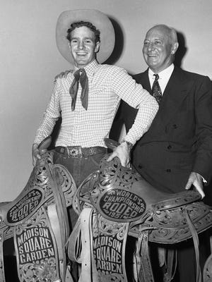 In this Oct. 21, 1951, file photo, rodeo legend Casey Tibbs, of Fort Pierre, S.D., poses with saddles in New York's Madison Square Garden after taking top honors in rodeo events in the World's Championship Rodeo. At right is Gen. John Reed Kilpatrick, president of Madison Square Garden. Denver filmmaker and South Dakota native Justin Koehler, who is producing a documentary about Tibbs, hopes to wrap up the project by the end of February 2016.