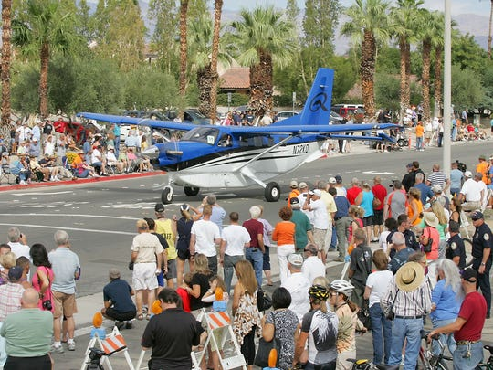 Spectators watch as the AOPA Aviation Summit's Parade of Planes makes its way to the Palm Springs Convention Center through the streets of Palm Springs in October 2012.   Organizers for the Flying Aviation Expo announced the conference will be cancelled this year.