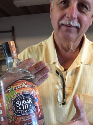 Bob Jordan shows off a bottle of his Sugar Tit Moonshine Simply Naked 100-proof corn whiskey.