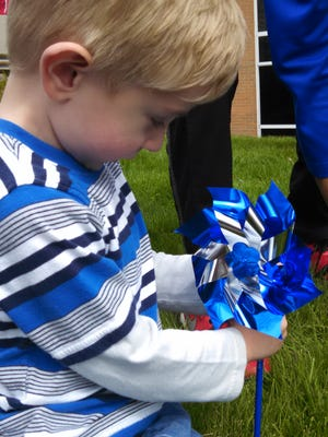 Three-year-old Elias Alexander plants a pinwheel in the lawn in front of The Villages in Indianapolis. Each pinwheel is meant to represent the carefree, happy life that a child should have.