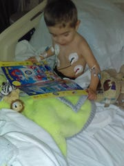 Gavin Ramirez, who suffered a stroke at the age of 4, plays in his Sparrow Hospital room after receiving a clot busting drug made for adults.